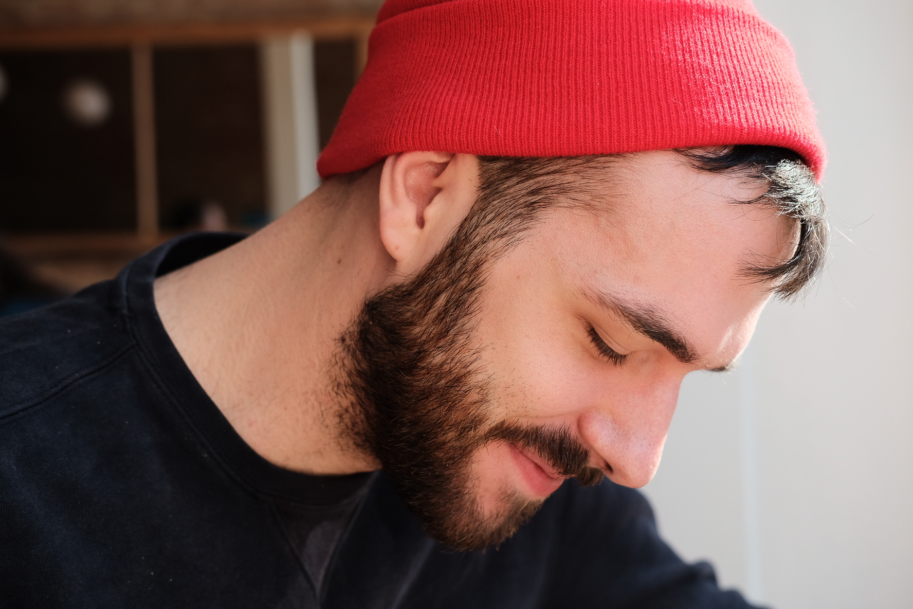 a photograph of Alex Evans. He has a beard and is wearing a red knit hat.